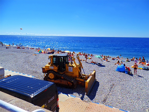 A bulldozer, leveling the pebbles on the beach. Nice, France.