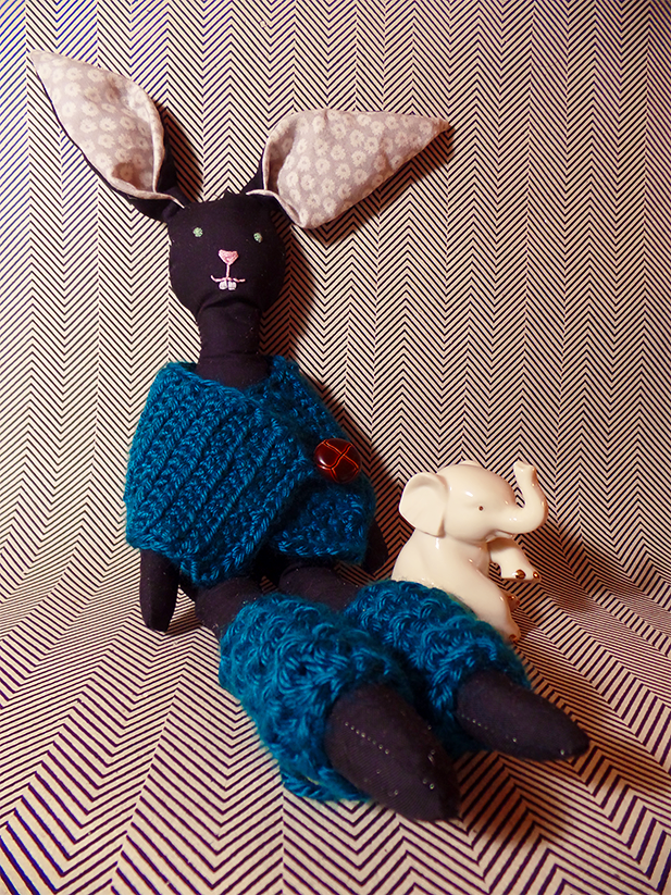 Handmade bunny modeling a handmade crocheted mini poncho and leg warmers.