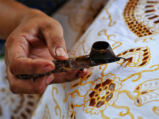 The canting tool used to lay wax on cloth during batik printmaking. Photo credit: Adwindo
